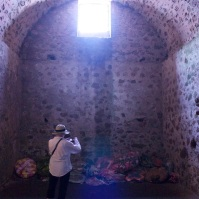 Inside one of the chambers of the male dungeon (turned into an offering and shrine), a tourist snaps a photo.