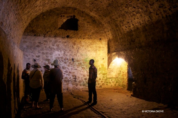 Inside a chamber of the male dungeon, three American tourists listen to tour guide Kwabena Kumi recount the history and circumstances of the location.