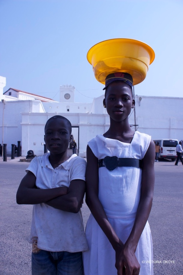 Two young street vendors sell sachet water to taxi drivers and tourists who patronize the castle and nearby areas.